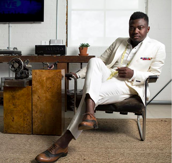 pictured: nana Bediako seated in a white suite with a sewing machine on a desk beside him